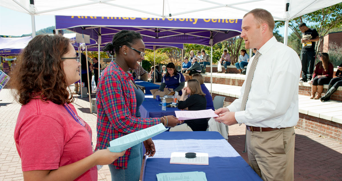 Advisor talking to students at information fair
