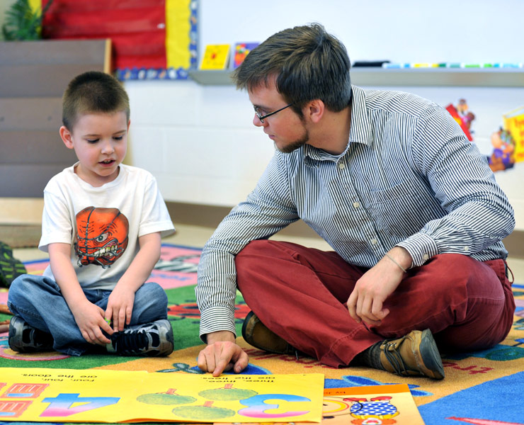 Elementary student teacher reading with a student
