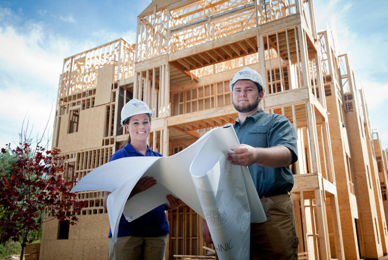 Two students wearing hardhats in front of a building under construction